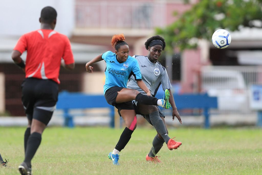 QPCC's Janine Francois, left, get a pass off while under pressure from Police Fc's Rhea Belgrave, right, during the Women's League Football (WOLF) match day 3 between QPCC and Police FC at New Settlement Grounds, Chaguanas in June.